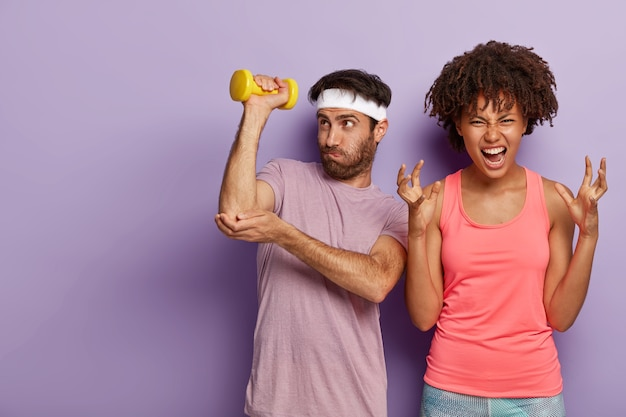 Unshaven guy raises arm with dumbbell, does exercises for training muscles and irritated curly haired woman gestures angrily, dissatisfied by something