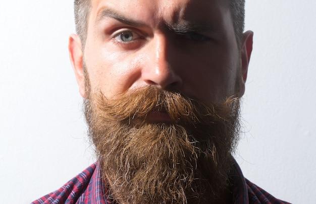 長いあごひげと口ひげのクローズアップで無精ひげを生やした男