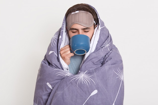 Unshaven male spending time at home in morning, man wrapped in blanket holding blue cup with hot beverage, enjoying drinking coffee