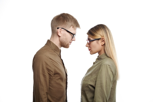 Unshaven man and blonde woman both in shirts and eyewear standing at white wall and looking at each other, their looks and postures expressing tension, rivalry and competition