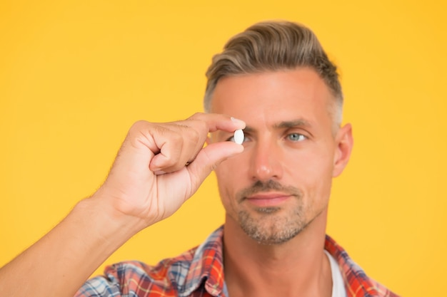 Unshaven man hold vitamin pill, selective focus. medicine concept. anabolic and steroids. food additives for male health. bio vitamin complex. disease treatment. presenting product. man look at drug.