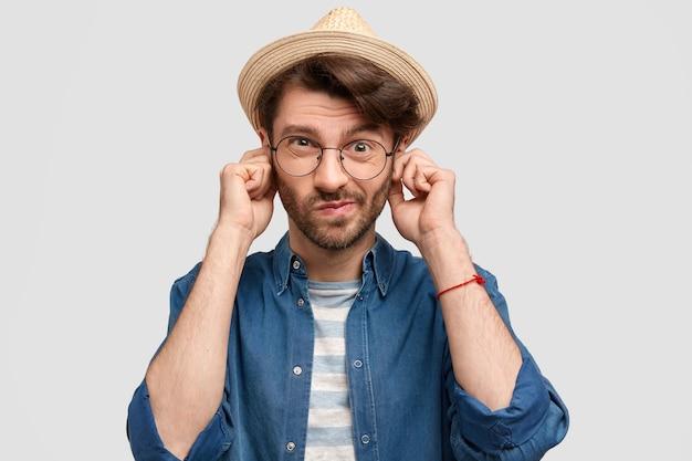 カジュアルな服装の無精ひげを生やした男は耳をふさぎ、迷惑な音を無視し、白い壁に隔離された不快な表情をしています。ハンサムな男が耳を覆う