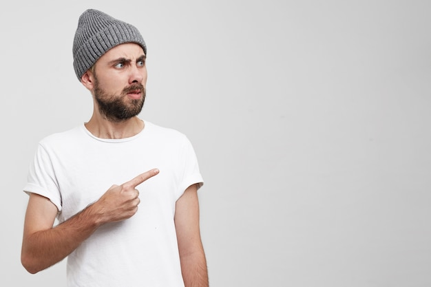 An unshaven man with a beard in a gray hat shows his index finger