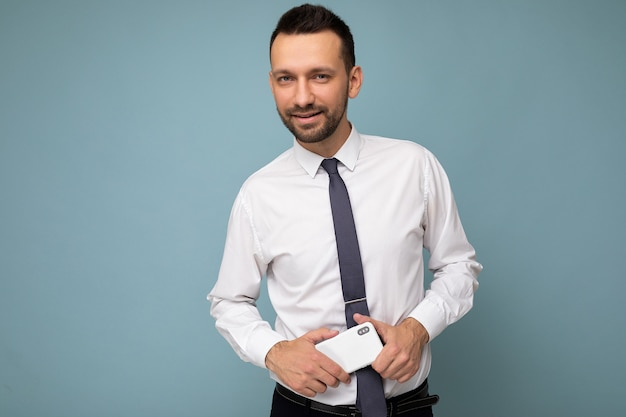 Unshaven man with beard wearing casual white shirt and tie isolated on blue wall with empty space holding in hand mobile phone .