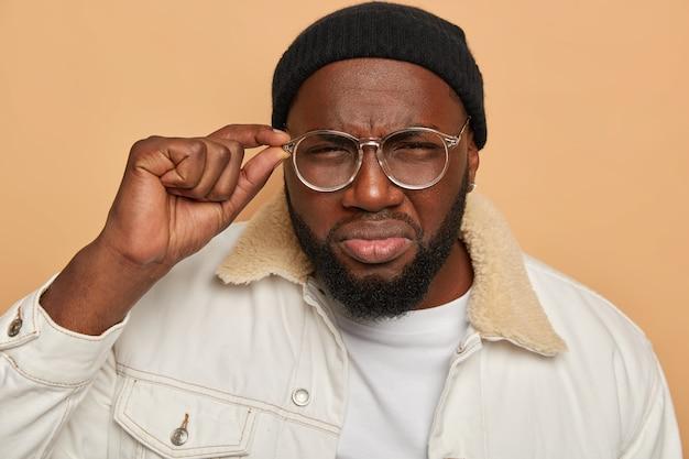 L'uomo nero triste con la barba lunga guarda scrupolosamente attraverso gli occhiali, cerca di vedere qualcosa