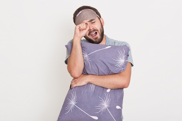 ひげを剃っていないあくびをして、屋内でポーズをとって、目をこすり、口を開いたままにし、灰色の枕を手に持って、朝起きている男