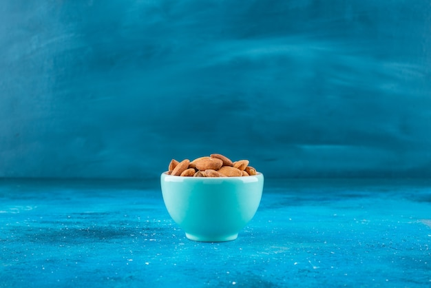 Unshelled almonds in a bowl on the blue surface
