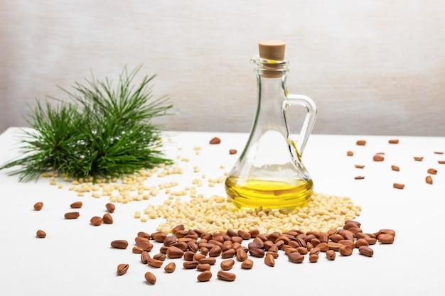 Unshelled cedar nuts. pine nut kernels and green pine tree branch. bottle of oil.