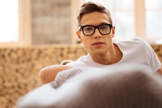 Без улыбки. привлекательный вдумчивый светловолосый молодой человек в очках и думает, сидя на диване