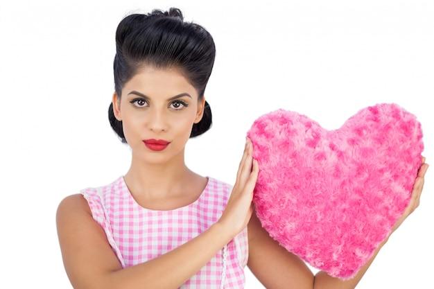분홍색 심장 모양의 베개를 들고 unsmiling 검은 머리 모델