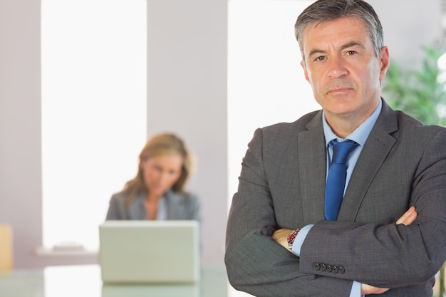 Unsmiling businessman looking at camera crossed arms with a businesswoman working on background