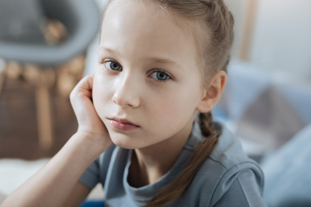 Unsmiling fair-haired blue-eyed little girl thinking and holding her head with her hand while sitting on the sofa