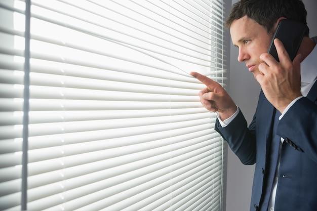Unsmiling handsome businessman looking through roller blind phoning
