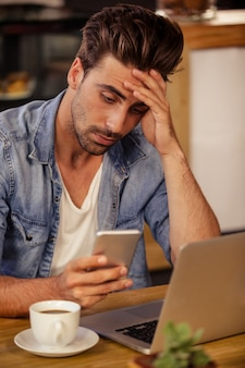 Unsmiling hipster man holding up his head while using smartphone