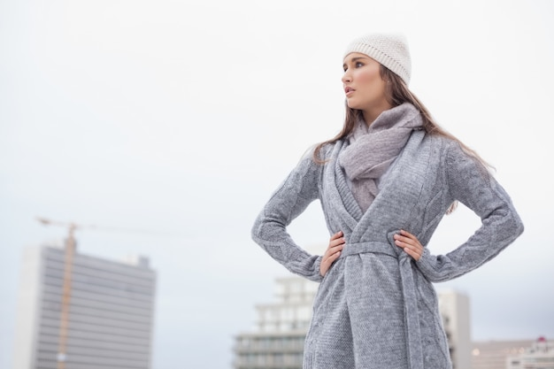 Unsmiling pretty brunette with winter clothes on posing