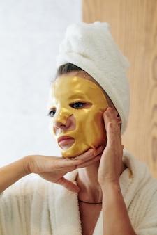 鏡、スキンケア、アンチエイジングトリートメントのコンセプトで自分自身を見ている彼女の顔に金色のゲルシートマスクとバスローブでニコリともしない女性