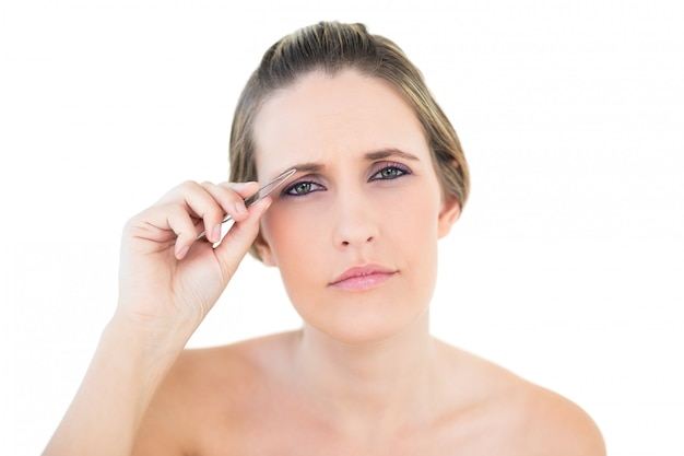 Unsmiling woman using tweezers looking at camera