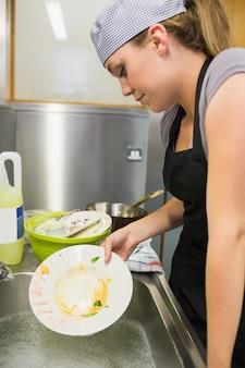 Unsmiling woman washing a plate