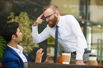 Unstable bearded boss gesturing at head while screaming
