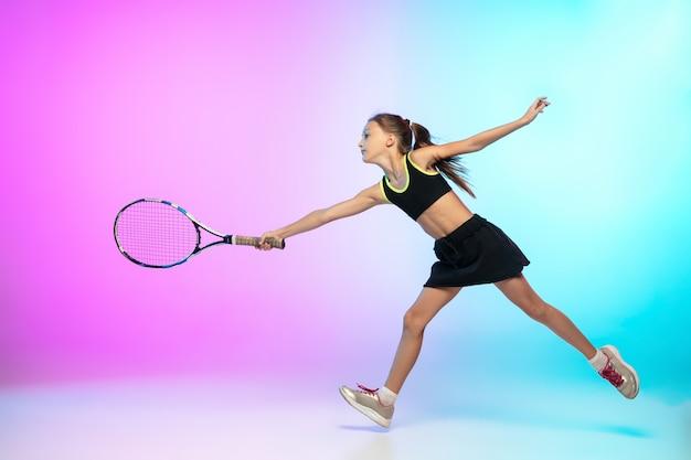 止められない。グラデーションの壁に分離された黒いスポーツウェアの小さなテニスの女の子
