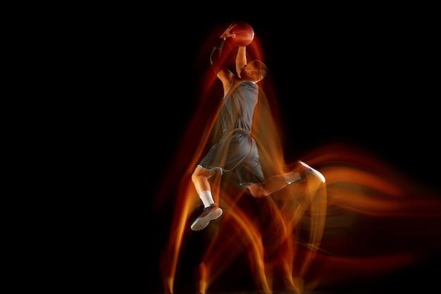 Неудержим. молодой восточноазиатский баскетболист в действии и движении, прыгающий в смешанном свете на темном фоне студии. понятие спорта, движения, энергии и динамичного, здорового образа жизни.