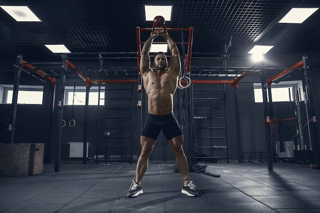 Unstoppable. young muscular caucasian athlete practicing squats in gym with the weight. male model doing strength exercises, training lower body. wellness, healthy lifestyle, bodybuilding concept.