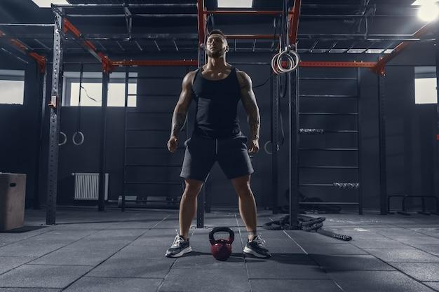멈출 수 없습니다. 무게와 체육관에서 스쿼트 연습 젊은 근육 백인 선수. 강도 운동을하는 남성 모델, 하체 훈련. 웰빙, 건강한 라이프 스타일, 보디 빌딩 개념.