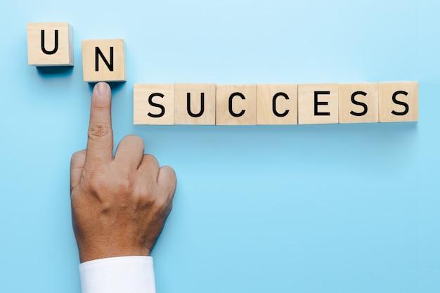 成功の概念への失敗、ビジネスマンの手が問題を押し出し、成功するビジネスへの障害