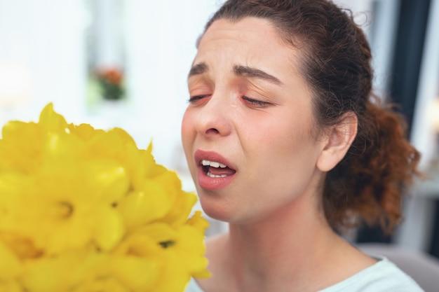 失敗したプレゼント。花粉に対する季節性アレルギーの突然の症状を経験している花の花束を提示されている思春期の女性