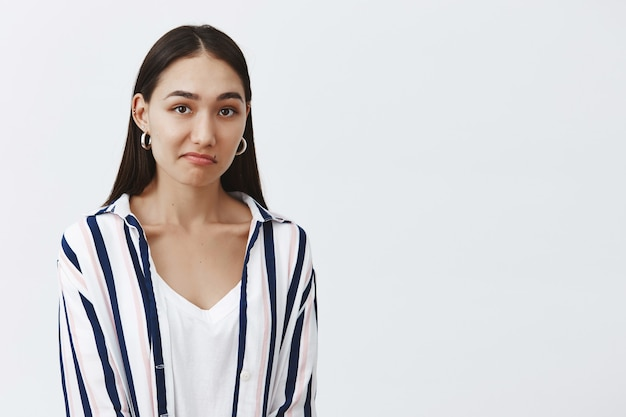 Unsure attractive and fashionable woman in striped blouse, pursing lip and gazing questioned, hesitating and wanting to reject offer politely, being displeased