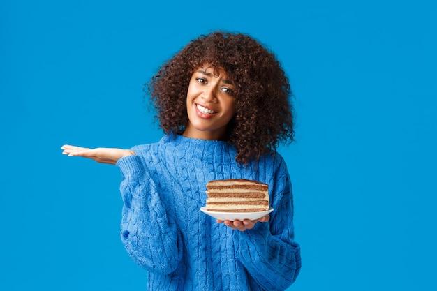Donna afroamericana attraente insicura e all'oscuro in maglione, scrollare le spalle sembra incerta, non so mangiare o no, tenendo il piatto con una gustosa torta piena di calorie, in piedi muro blu.