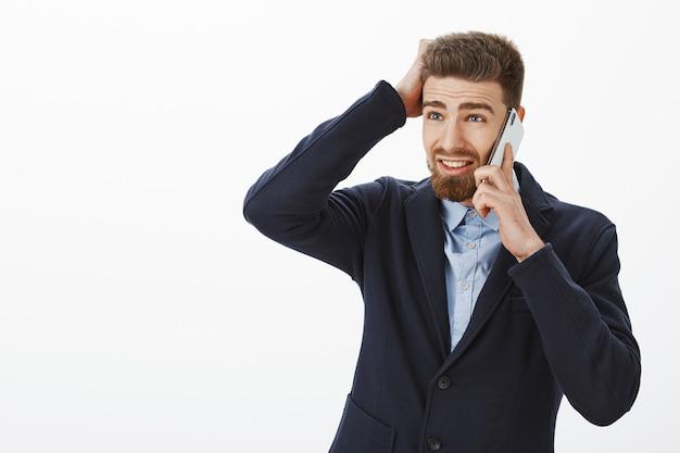 수염을 가진 우아한 정장을 입고 혼란스러워하는 매력적인 남성 기업가가 회색 벽을 통해 늦게 일하기 위해 핸드폰을 통해 사과하는 스마트 폰으로 말하는 문제가있는 얼굴로 왼쪽을 보았습니다.
