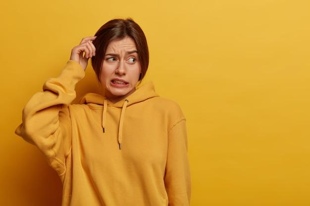 Unsure doubtful woman scratches head, has amnesia, makes tough decision, looks troubled aside, stands puzzled, clenches teeth, dressed in hoodie, poses against yellow wall, empty space for text