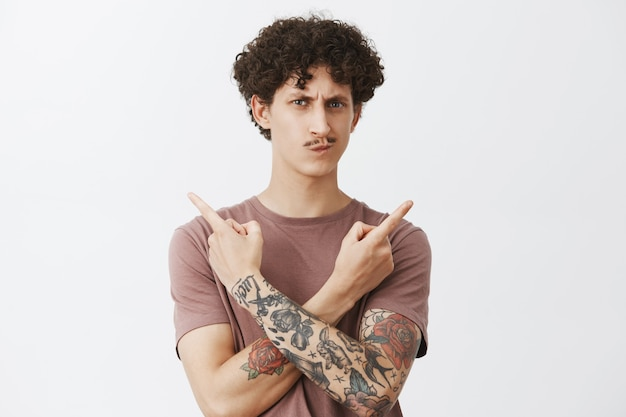 Неуверенный нерешительный симпатичный молодой парень с вьющимися темными волосами и причудливыми усами ухмыляется и хмурится, подозрительно и сомнительно указывая влево и вправо в разные стороны, не может выбрать, что выбрать