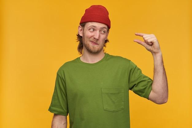 Неуверенно выглядящий мужчина, красивый бородатый парень со светлыми волосами. в зеленой футболке и красной шапке. показывает небольшой размер и смотрит на него с сомнением. стенд изолирован над желтой стеной