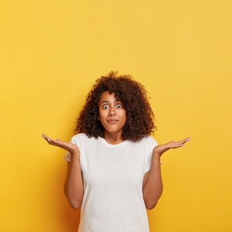 Unsure puzzled female student spreads palms sideways, stares with bugged eyes, being clueless and unaware, has dark curly hair, wears white t shirt, poses against yellow wall, free space upwards