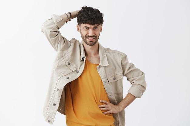Неуверенный в себе серьезный стильный бородатый парень позирует у белой стены