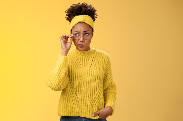 Unsure thoughtful hesitant cute african-american millennial teenage girl in round glasses sweater headband solving riddle mind look up doubtful touch eyewear smirking, thinking yellow background.
