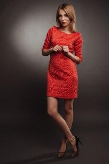 灰色で隔離の赤いドレスの若い金髪実業家がわからない