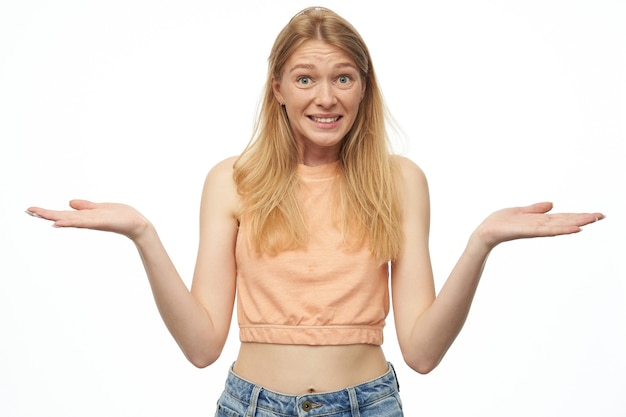 Unsure young lady wears orange top and denim pants on white