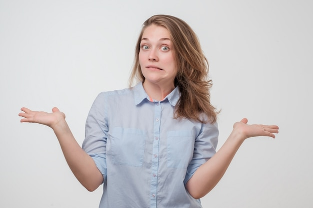 Unsuspecting woman shrugs shoulders of helplessness being unsure