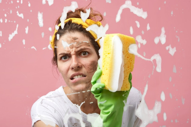 Untidy angry female with dirt on her face wearing casual clothes and green rubber gloves while tidying up in apartment, washing mirror or window glass using cleaning spray and sponge.