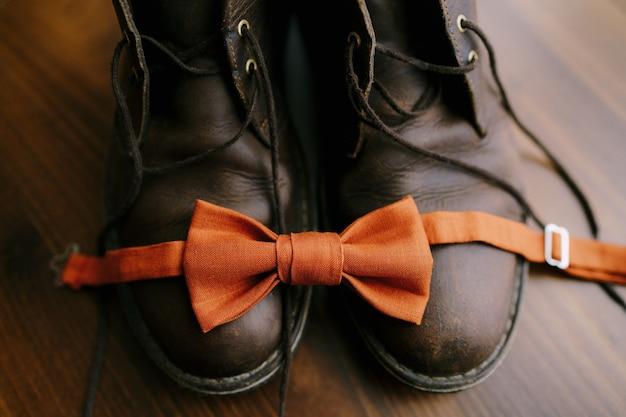 망 부츠에 묶이지 않은 주황색 신랑 나비 넥타이