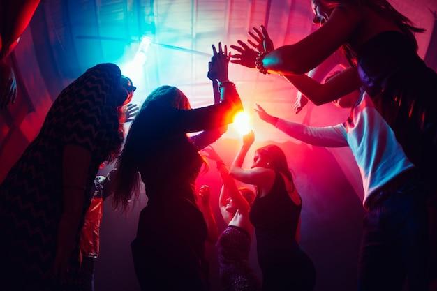 日の出まで。シルエットの人々の群衆は、ネオンの光の背景のダンスフロアに手を上げます。ナイトライフ、クラブ、音楽、ダンス、モーション、若者。パープルピンクの色と感動的な女の子と男の子。