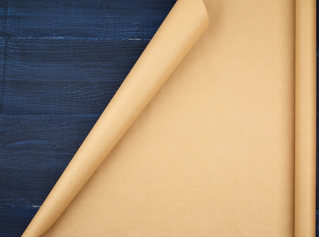 Untwisted roll of brown craft paper on a blue wooden background