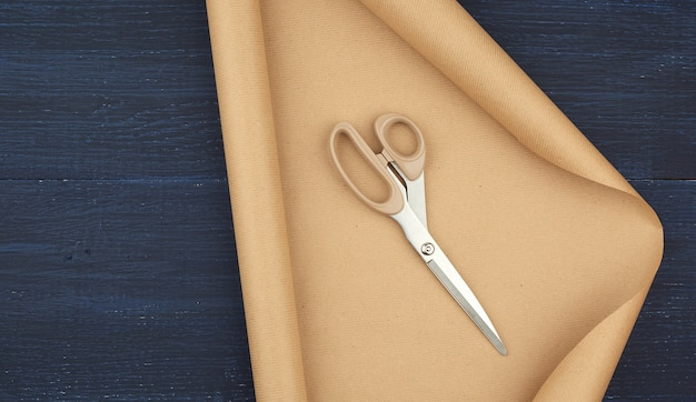 Untwisted roll of brown craft paper on a blue wooden