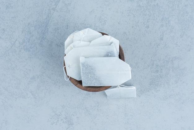 Bustine di tè inutilizzate in una ciotola su marmo.
