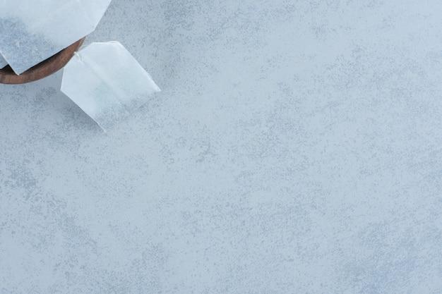 Неиспользованные чайные пакетики в миске на мраморе.