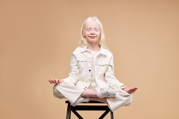 Необычный инопланетный ребенок-альбинос сидит в изолированной позе йоги