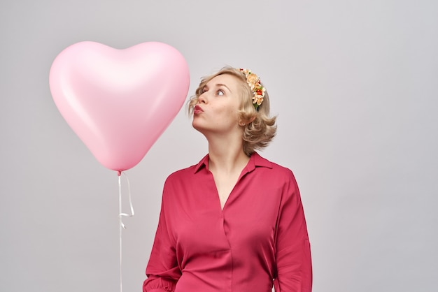 Необычная привлекательная молодая девушка в красном платье и с венком на голове держит воздушный шарик в форме сердца и целует его. концепция любви, день святого валентина, удивит любимого